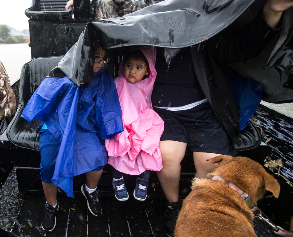 . Jacob and Gracie Velasco take cover under a tarp as they are evacuated from their home as water rises from heavy rains from Tropical Storm Harvey on Monday, Aug. 28, 2017, in Fort Bend County, Texas. (Brett Coomer/Houston Chronicle via AP)