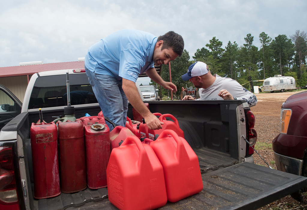 . Robert Dressell of Tyler and Adam Turner of Tyler pack the back of a pickup truck with fuel before leaving from WC Custom Boats in Noonday, Texas to head to areas affected by Hurricane Harvey Monday morning, Aug. 28, 2017. The group took six boats stocked with fuel and water headed to the Houston area to assist in Hurricane Harvey rescue efforts. (Sarah A. Miller/Tyler Morning Telegraph via AP)