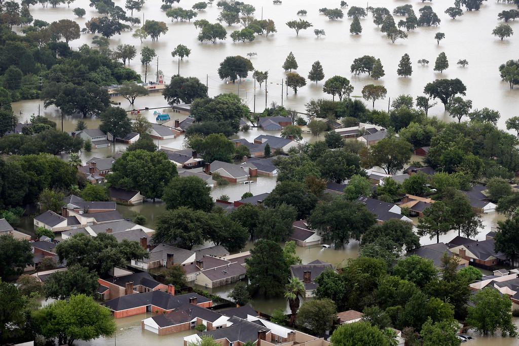""". Homes in a neighborhood are flooded near the Addicks Reservoir as floodwaters from Tropical Storm Harvey rise Aug. 29, 2017, in Houston. Officials working in the area say some homes will be  inundated \""""for up to a month.\"""" AP Photo/David J. Phillip"""