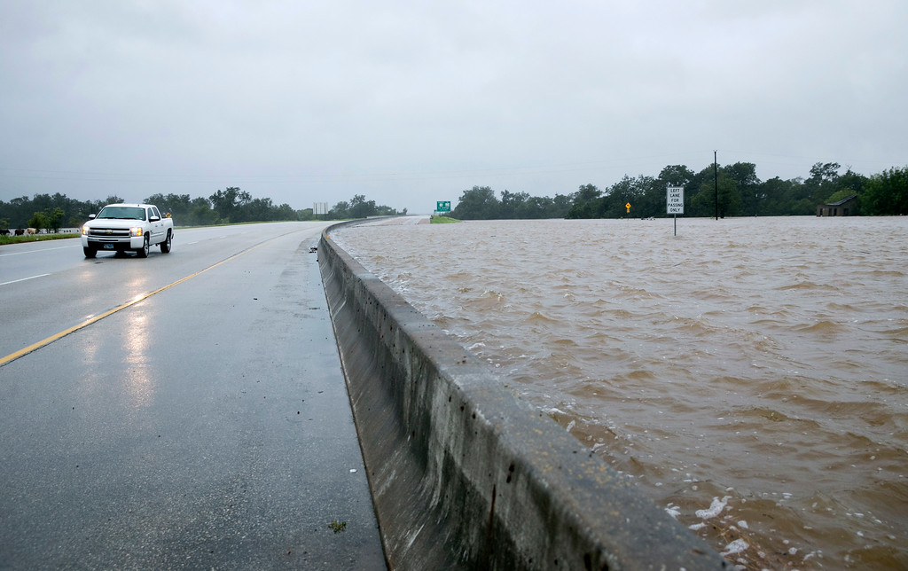 . The westbound lanes of Highway 71 in La Grange, Texas, at the Colorado River are underwater after Hurricane Harvey on Monday, Aug. 28, 2017. The center highway barricade is all that\'s holding back the water from spilling into the eastbound lanes. (Jay Janner/Austin American-Statesman via AP)