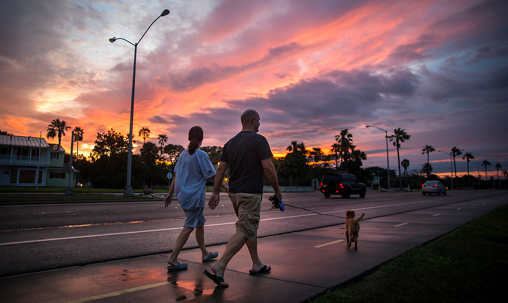 . A couple walks their dog along Ocean Drive in Corpus Christi, Texas, on Saturday, Aug. 26, 2017. Hurricane Harvey hit the Texas coast late Friday as a Category 4 storm, damaging buildings and leaving tens of thousands without power. (Nick Wagner /Austin American-Statesman via AP)
