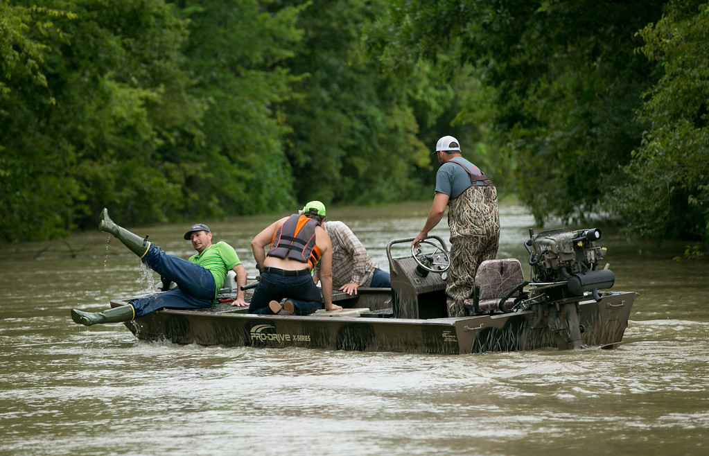 . A man drains his boots while preparing to rescue cattle from the Liberty Bell Ranch in the wake of Tropical Storm Harvey Wednesday, Aug. 30, 2017 in Liberty, Texas. The volunteers were traveling along Highway 90 when they stopped to help.   (Jay Janner/Austin American-Statesman via AP)