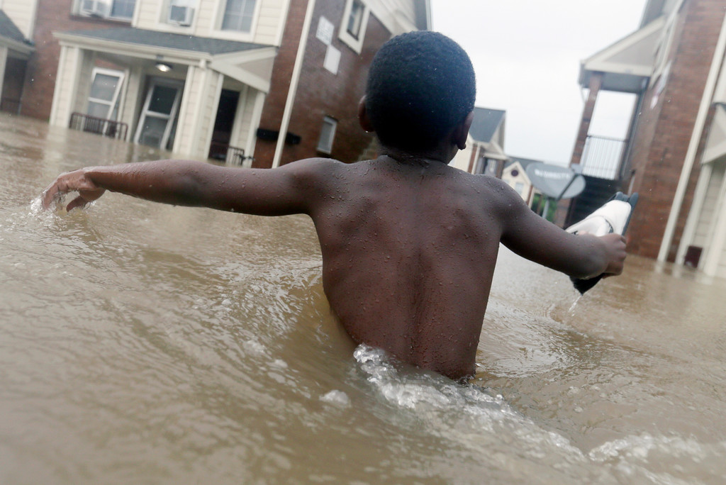 . Jayveon Murphy, 10, makes is way through floodwaters from Tropical Storm Harvey to check on a neighbor at his apartment complex in Houston, Sunday, Aug. 27, 2017. The remnants of Hurricane Harvey sent devastating floods pouring into Houston Sunday as rising water chased thousands of people to rooftops or higher ground. (AP Photo/LM Otero)