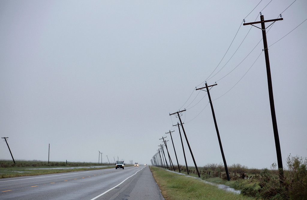 . Power lines slant on SH 35 heading from Rockport to Victoria, Texas Sunday, Aug. 27, 2017. The area was hit by Hurricane Harvey. (The Victoria Advocate via AP)