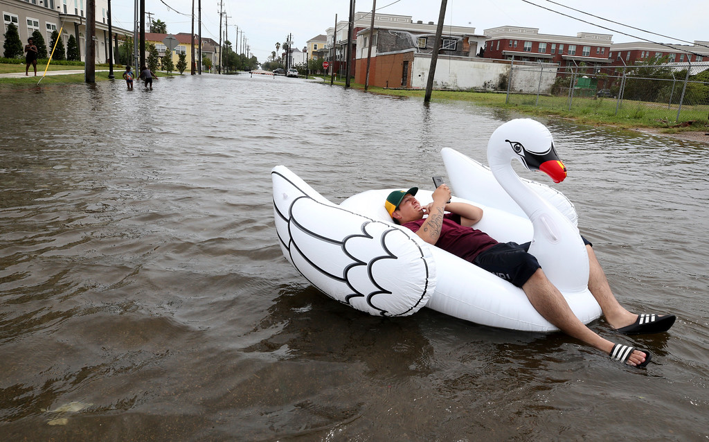 . Julio Ostio sits in an inflatable swan as he floats down 16th Street near Strand Street in Galveston, Texas, on Saturday, Aug. 26, 2017, as he texts friends during a break in the rain from Hurricane Harvey. (Jennifer Reynolds/The Galveston County Daily News via AP)