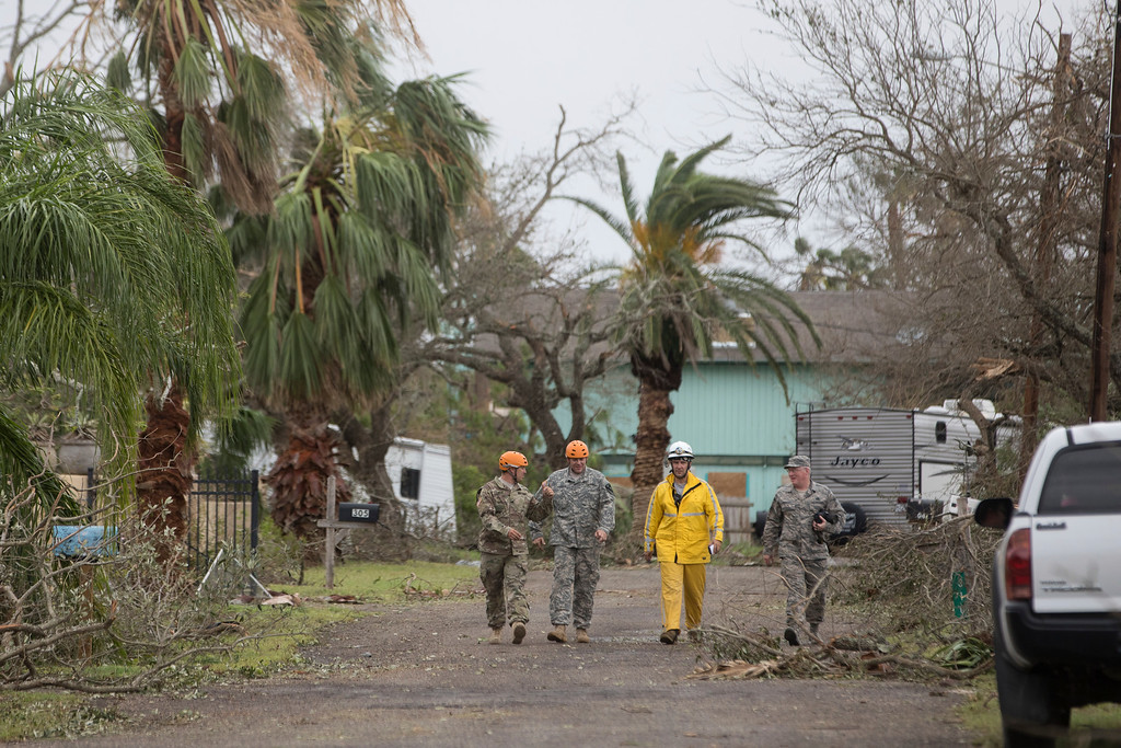 . Members of the Texas National Guard Sunday walk through a Fulton Texas neighborhood Sunday, Aug. 27, 2017. Hurricane Harvey made landfall in Texas on Friday night as the strongest hurricane to hit the U.S. in more than a decade. (Courtney Sacco/Corpus Christi Caller-Times via AP)