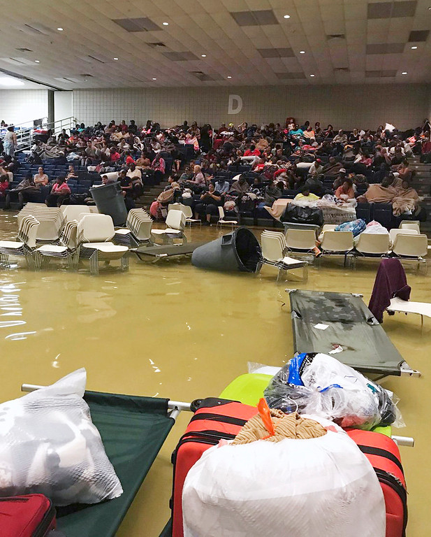 . Evacuees sit in the bleachers at the Bowers Civic Center in Port Arthur, Texas, Aug. 30, 2017, after floodwaters caused by Tropical Storm Harvey inundated the facility overnight. Authorities said it\'s not clear where the evacuees will go. Beulah Johnson via AP