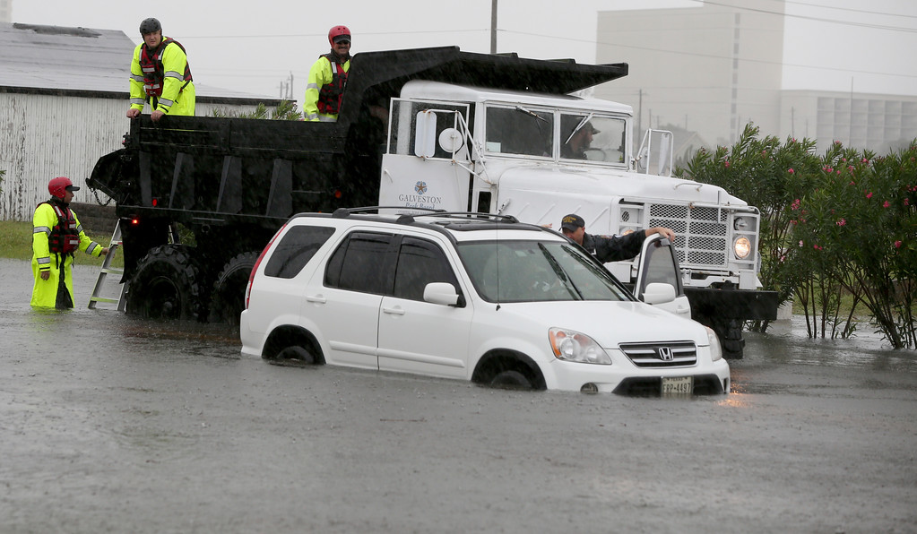 . Members of the Galveston Police Dive Team assist a motorist who stalled her vehicle in high water on Avenue T 1/2 at 61st Street in Galveston, Texas on Tuesday, Aug. 29, 2017. Heavy rains from Tropical Storm Harvey have flooded roads across the island. Floodwater was also getting into business in downtown. (Jennifer Reynolds/The Galveston County Daily News via AP)