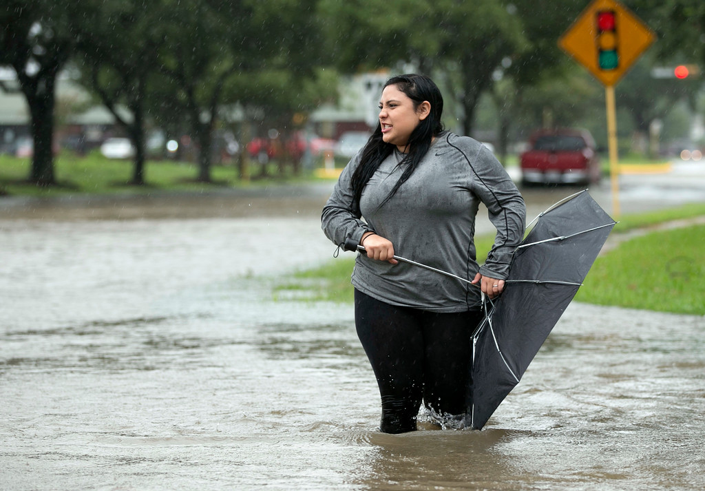 . Daisie Perez struggles with an umbrella while looking at the rising floodwaters in her northwest Houston neighborhood as floodwaters from Tropical Storm Harvey rise Monday, Aug. 28, 2017. (Jay Janner/Austin American-Statesman via AP)