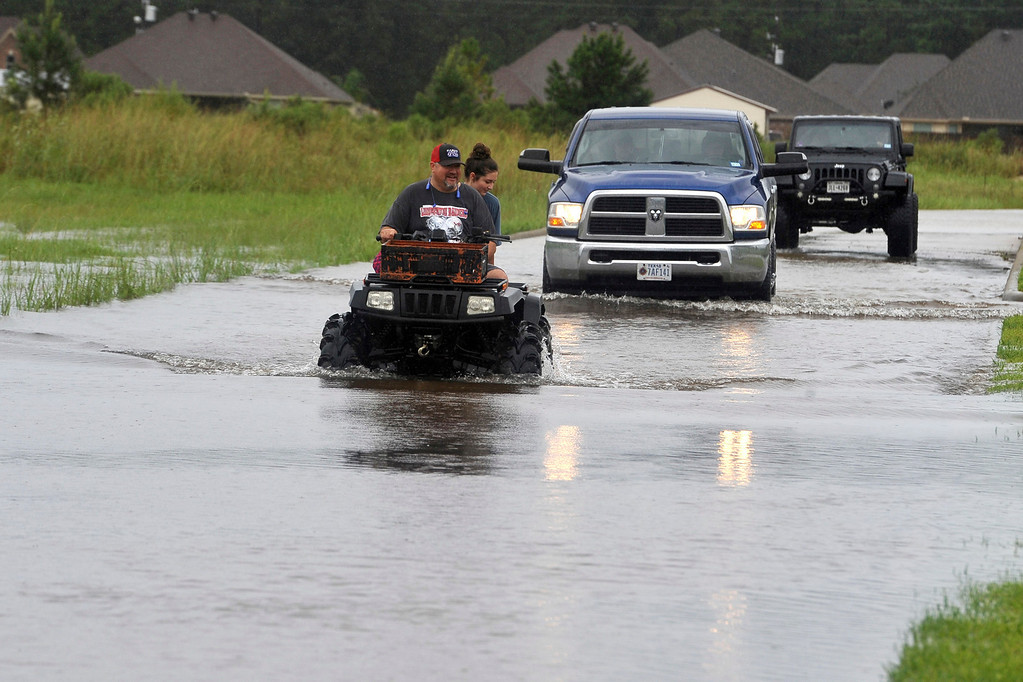 . Jason Hendry drives his daughter, Callie, out of Westwood Heights on his ATV in Lumberton, Texas, on Sunday, Aug. 27, 2017. The remnants of Hurricane Harvey sent devastating floods pouring into Houston Sunday as rising water chased thousands of people to rooftops or higher ground. (Ryan Pelham/The Beaumont Enterprise via AP)