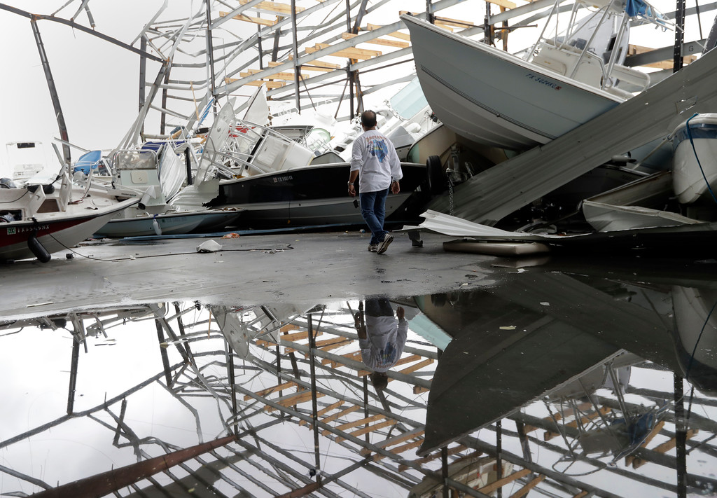 . Dominic Dominguez looks through a stack of boats jumbled in the wake of Hurricane Harvey, Sunday, Aug. 27, 2017, in Rockport, Texas. (AP Photo/Eric Gay)