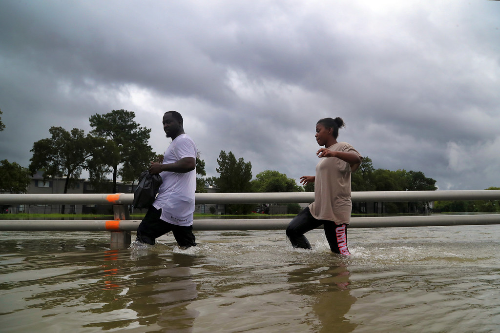 . Residents walk through high waters, the remnants of Hurricane Harvey, on Watonga Boulevard, Sunday, Aug. 27, 2017, in Houston. The remnants of Hurricane Harvey sent devastating floods pouring into Houston Sunday as rising water chased thousands of people to rooftops or higher ground. (Marie D. De Jesus/Houston Chronicle via AP)