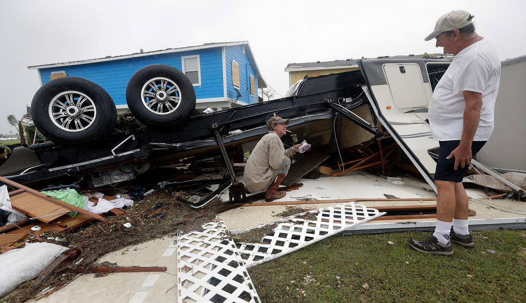 . Richard Garner, right, and friend Mark Richard, left, look through the remains of Garner\'s RV that was damaged in the wake of Hurricane Harvey, Monday, Aug. 28, 2017, in Rockport, Texas. (AP Photo/Eric Gay)