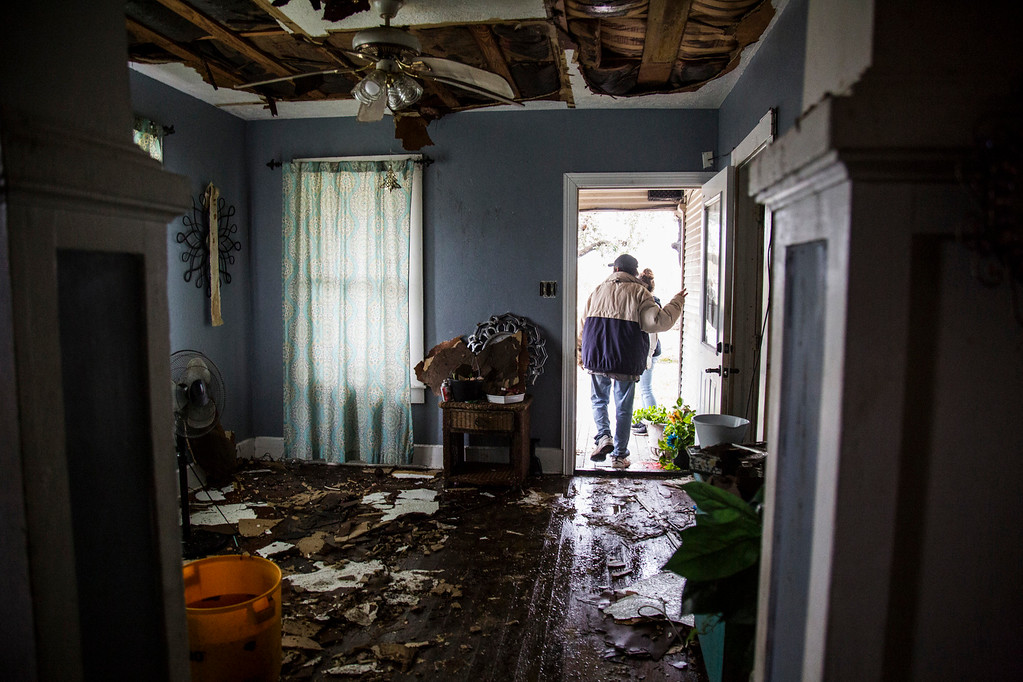 . Lucas Garcia walks out of his home in Refugio, Texas on Aug. 26, 2017. Garcia and other family members rode out Hurricane Harvey in a single room in their home (Olivia Vanni/The Victoria Advocate via AP)