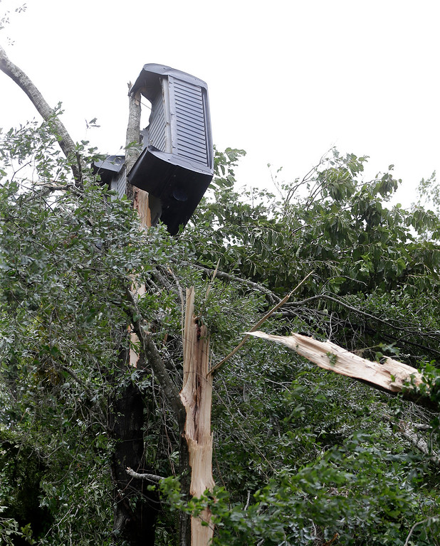 . A truck bed lies in a tree near Bryant\'s Auto Sales in Katy, Texas, on Saturday, Aug. 26, 2017, after a possible tornado during Hurricane Harvey. ( Melissa Phillip /Houston Chronicle via AP)