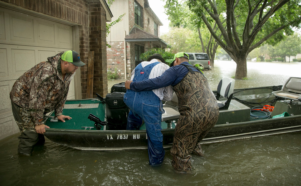 . Thomas Luna, left, and Hugo Elizonda, right, rescue Bobby Nelson, 78, from his flooded home in the Ravensway neighborhood in northwest Houston after Hurricane Harvey, Monday, Aug. 28, 2017. Luna and Elizondo came with a fishing boat to help with the rescue effort. (Jay Janner/Austin American-Statesman via AP)