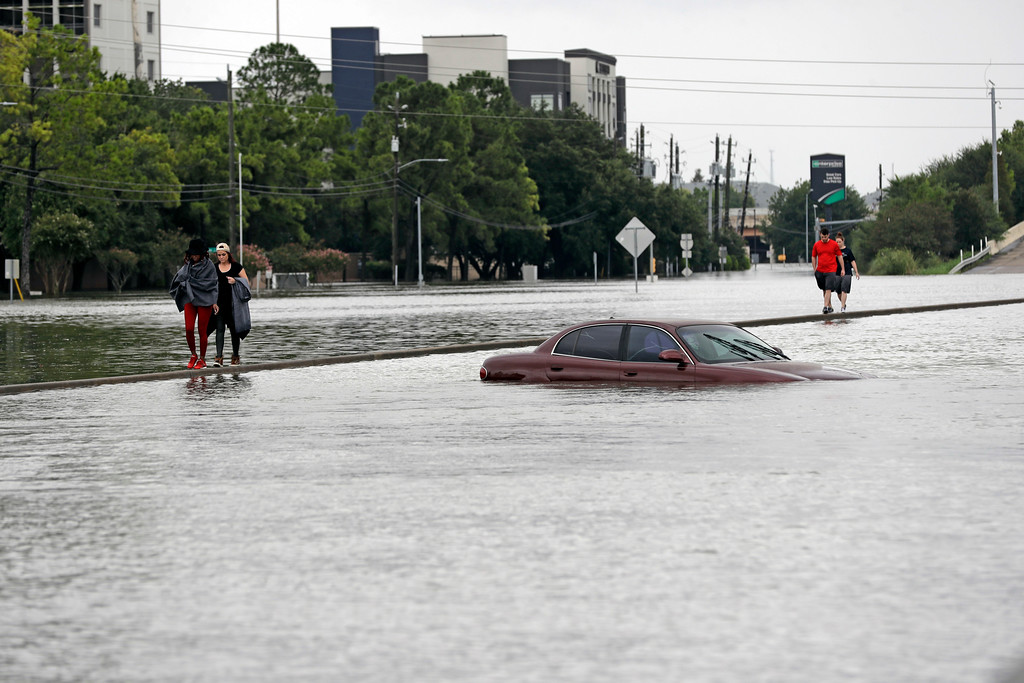 . Evacuees walk along a median of Interstate 610 covered in floodwaters from Tropical Storm Harvey Sunday, Aug. 27, 2017, in Houston. The remnants of Hurricane Harvey sent devastating floods pouring into Houston Sunday as rising water chased thousands of people to rooftops or higher ground. (AP Photo/David J. Phillip)