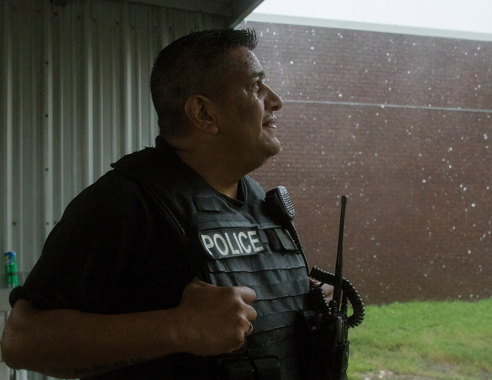 . Lt. Javier Ramos, of the Port Lavaca Police Department, looks up at the rain while other officers eat barbecue chicken on Friday, Aug. 25, 2017. The officers were unable to respond to emergencies after winds reached 40 mph. Hurricane Harvey smashed into Texas late Friday, lashing a wide swath of the Gulf Coast with strong winds and torrential rain from the fiercest hurricane to hit the U.S. in more than a decade. (Ana Ramirez/The Victoria Advocate via AP)