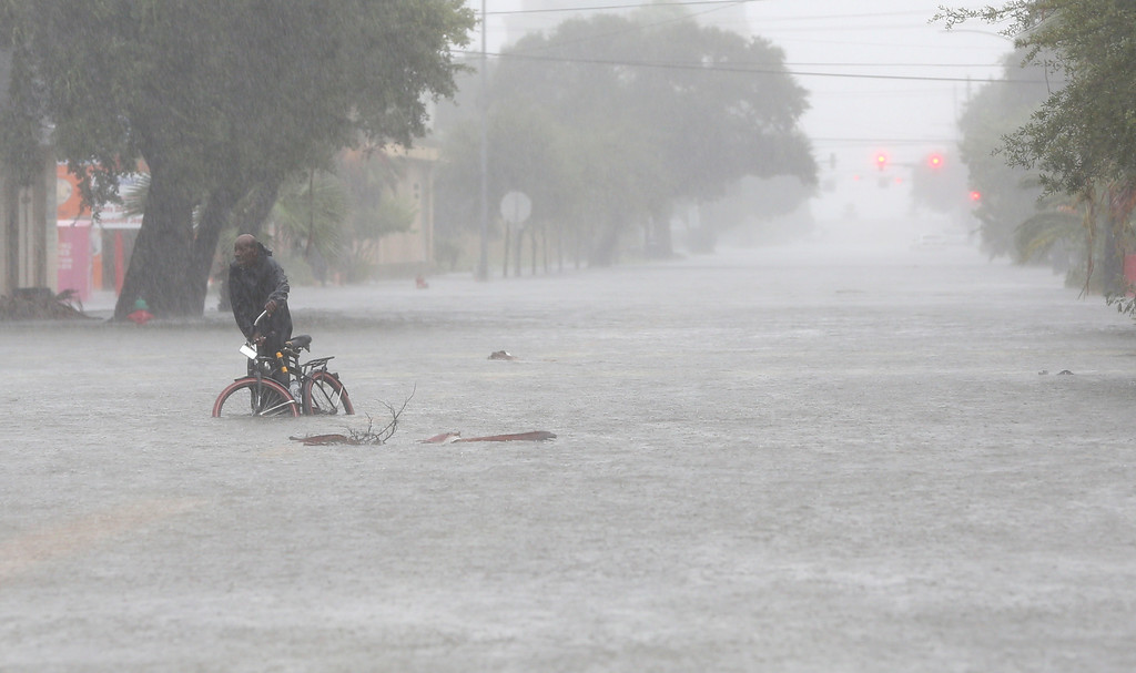 . A man pushes his bicycle through floodwaters on 23rd Street near Broadway in Galveston, Texas on Tuesday, Aug. 29, 2017. Heavy rains from Tropical Storm Harvey have inundated much of the island. (Jennifer Reynolds/The Galveston County Daily News via AP)