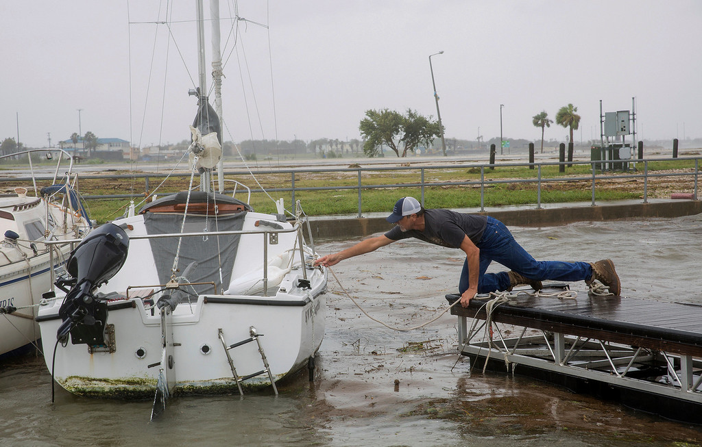 . Mike Bush, 56, ties a loose boat with a rope in Port Lavaca, Texas, Sunday, Aug. 27, 2017. Other boats at the harbor were damaged by loose boats and high winds during Hurricane Harvey. The National Weather Service said winds in Port Lavaca, Texas reached 49 mph during the storm. (Ana Ramirez/The Victoria Advocate via AP)