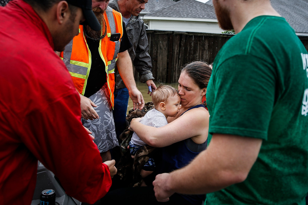 . Lauren Durst holds onto her ten-month-old son, Wyatt Durst, as they evacuate from the Savannah Estates neighborhood as Addicks Reservoir nears capacity during Tropical Storm Harvey, Tuesday, Aug. 29, 2017, in Houston. Michael Ciaglo/Houston Chronicle via AP