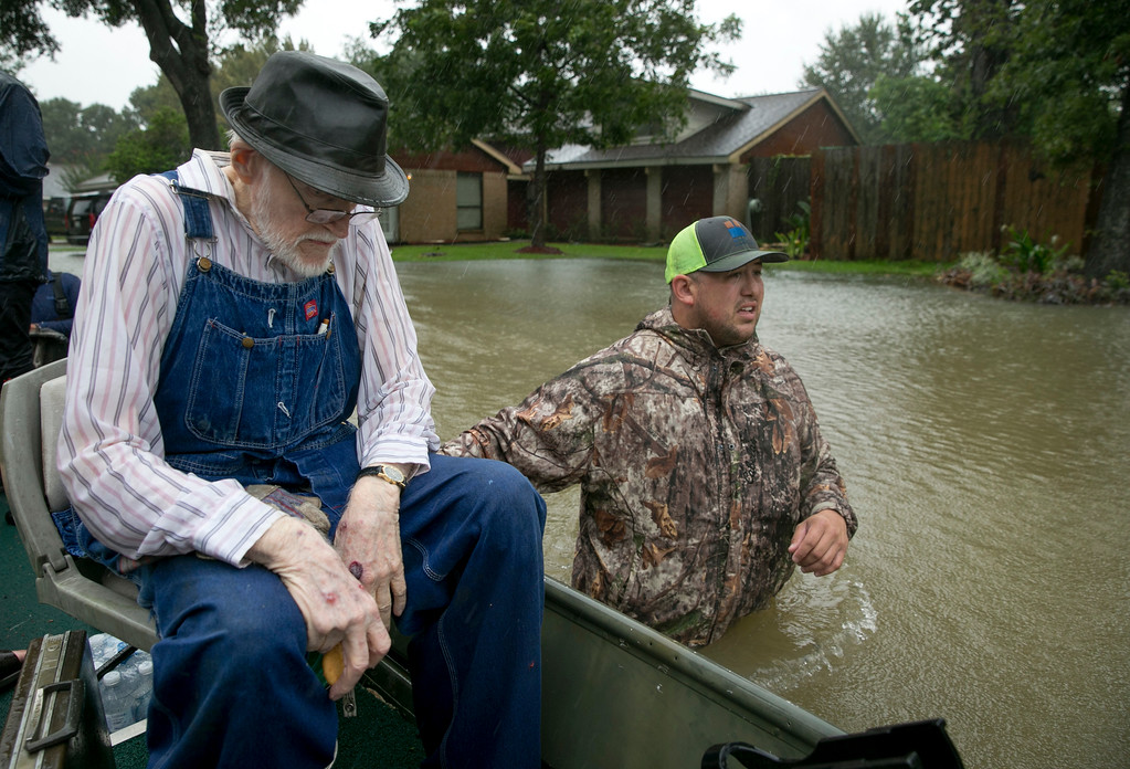 . Thomas Luna, right, rescues Bobby Nelson, 78, from his flooded home in the Ravensway neighborhood in northwest Houston after Hurricane Harvey, Monday, Aug. 28, 2017. Luna came with a fishing boat to help with the rescue effort. (Jay Janner)/Austin American-Statesman via AP)
