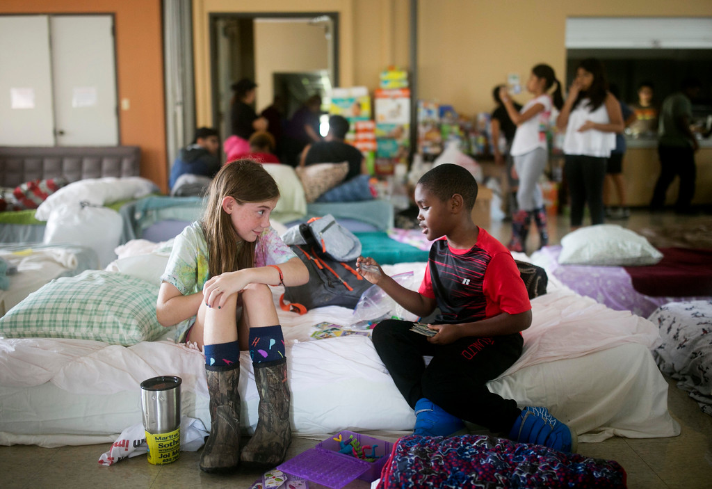 . Volunteer Elizabeth Hill, 8, plays with evacuee Skyler Smith, 7, at a shelter at St. Thomas Presbyterian Church in west Houston as Tropical Storm Harvey continues to affect the area Tuesday, Aug. 29, 2017. Jay Janner/Austin American-Statesman via AP