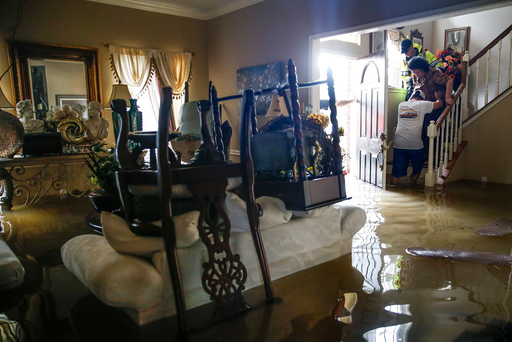 . Chris Gutierrez, left, helps his grandmother, Edelmira Gutierrez, down the stairs of their flooded house and into a waiting fire department truck in the Concord Bridge neighborhood as Addicks Reservoir surpasses capacity. Michael Ciaglo/Houston Chronicle via AP
