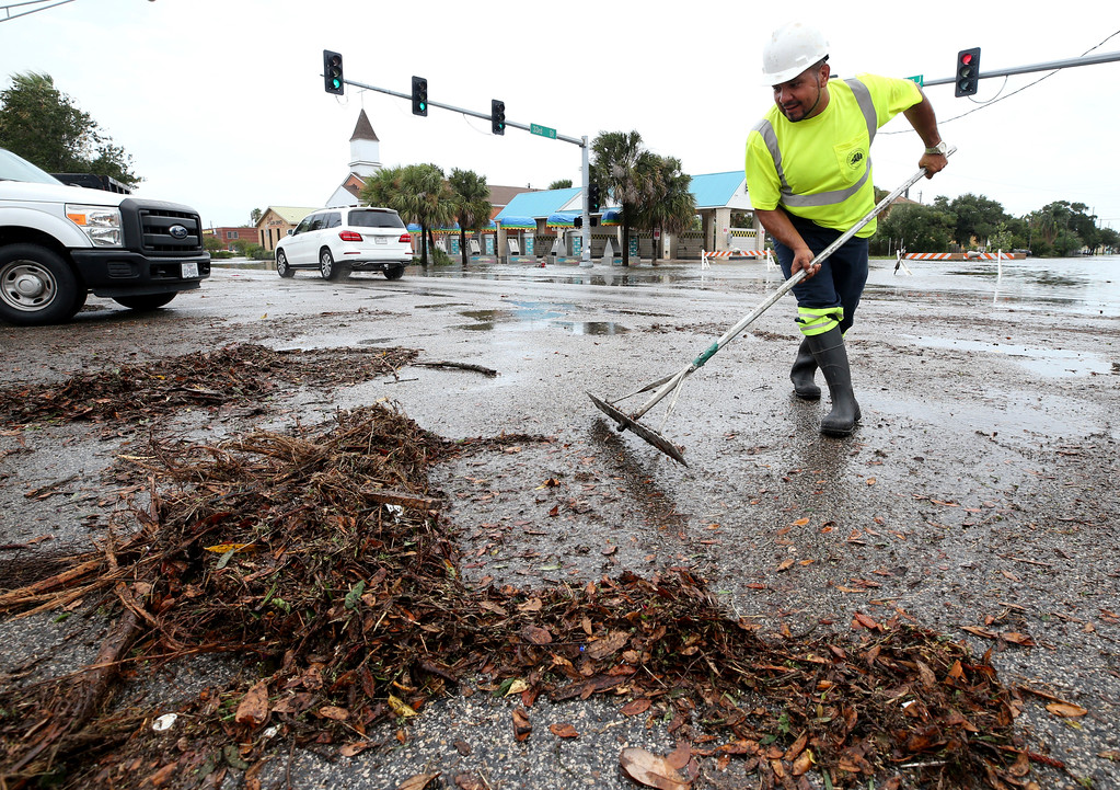 . German Martinez, with Galveston\'s Public Works department, clears debris from the intersection of 33rd Street and Broadway on Saturday, Aug. 26, 2017, as high waters from Hurricane Harvey begin to recede. (Jennifer Reynolds/The Galveston County Daily News via AP)