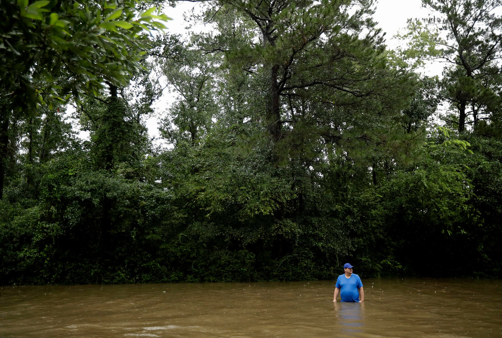 . A man stands in floodwaters from Tropical Storm Harvey as he waits to board a boat to help look for evacuees Tuesday, Aug. 29, 2017, in Kingwood, Texas. AP Photo/Gregory Bull