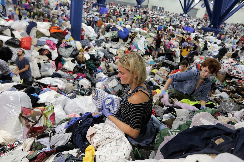 . Kathryn Loder sorts donated clothing at George R. Brown Convention Center in Houston as Tropical Storm Harvey inches its way through the area on Tuesday, Aug. 29, 2017.  Elizabeth Conley/Houston Chronicle via AP