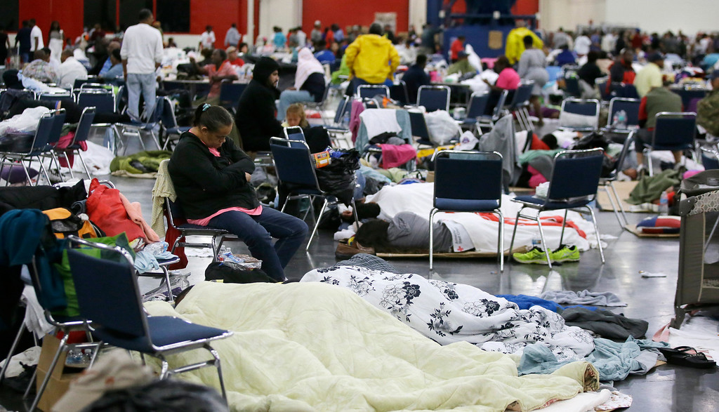 . People rest at the George R. Brown Convention Center that has been set up as a shelter for evacuees escaping the floodwaters from Tropical Storm Harvey in Houston on Tuesday, Aug. 29, 2017. AP Photo/LM Otero