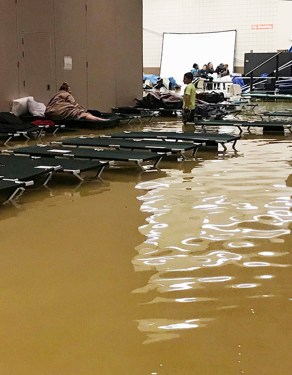 . In this photo provided by Beulah Johnson, people inside the Bowers Civic Center in Port Arthur, Texas, Aug. 30, 2017, are surrounded by floodwaters caused by Tropical Storm Harvey that overcame the facility that was being used as a shelter for those seeking refuge from the storm. Beulah Johnson via AP