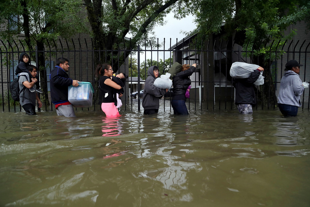 . Residents from Bayou Parc at Oak Forest carry their belongings while evacuating the apartment complex during the Tropical Storm Harvey, Sunday, Aug. 27, 2017, in Houston.  The remnants of Hurricane Harvey sent devastating floods pouring into Houston Sunday as rising water chased thousands of people to rooftops or higher ground. (Marie D. De Jesus/Houston Chronicle via AP)