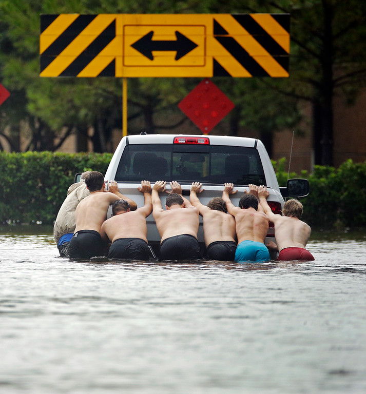 . People push a stalled pickup to through a flooded street in Houston, after Tropical Storm Harvey dumped heavy rains Sunday, Aug. 27, 2017. The remnants of Hurricane Harvey sent devastating floods pouring into Houston Sunday as rising water chased thousands of people to rooftops or higher ground. (AP Photo/Charlie Riedel)