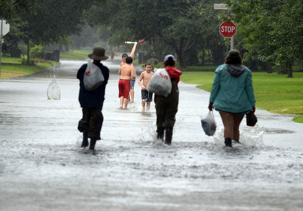 . Three boys play baseball on 22nd Street in Beaumont, Texas while three other people return home with supplies during Sunday\'s stormy weather, the remnants of Hurricane Harvey, Sunday, Aug. 27, 2017. (Guiseppe Barranco/The Beaumont Enterprise via AP)