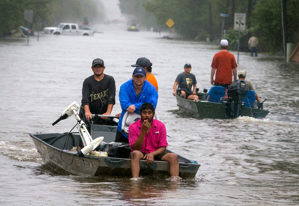 . People in a boat make their way down Deats Road in Dickinson, Texas, Monday, Aug. 28, 2017, as floodwaters from Tropical Storm Harvey rise. (Stuart Villanueva/The Galveston County Daily News via AP)