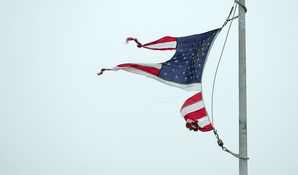 . A tattered U.S. flag whips in the wind in Geronimo, Texas, during Hurricane Harvey on Saturday August 26, 2017. (Jay Janner/Austin American-Statesman via AP)