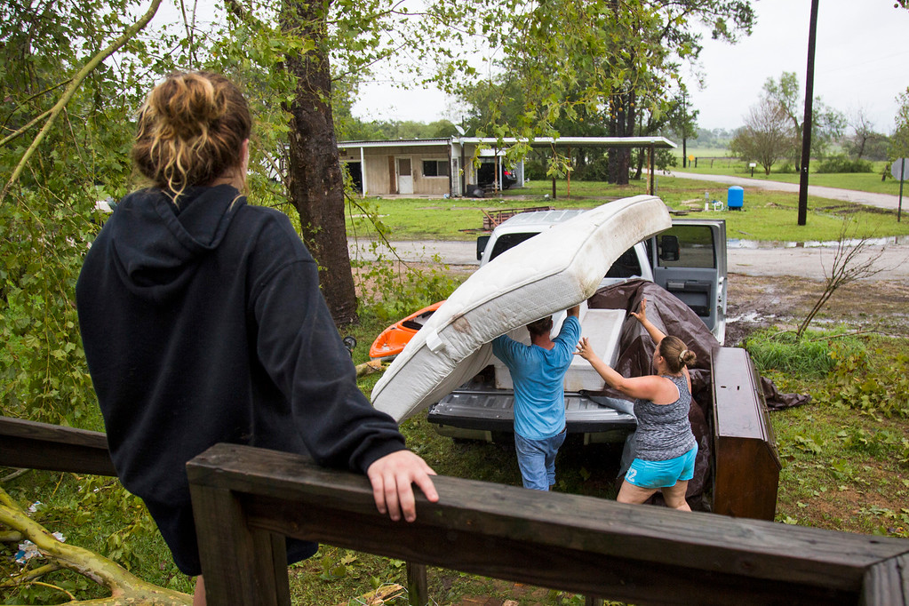 . Kaylee Kainer, 16, left, watches as Aaron Whitfield, 37, and Alisha Dement, 39, load a mattress into the back of their truck at River Haven in Cuero, Texas Monday, Aug. 28, 2017, after Tropical Storm Harvey went through the area.  (The Victoria Advocate via AP)