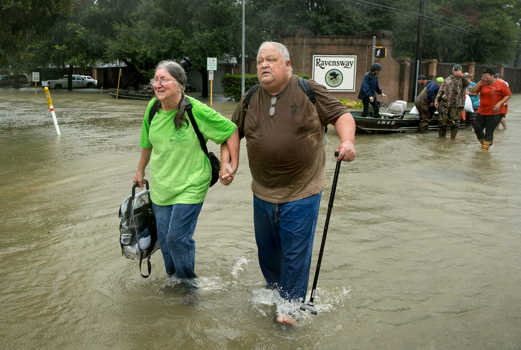 . Margie David and her husband David Emswiler walk away after being rescued by volunteers on a boat from the flooded house in northwest Houston after Hurricane Harvey, Monday, Aug. 28, 2017. (Jay Janner)/Austin American-Statesman via AP)