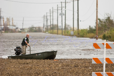 A Wildlife and Fisheries agent drives a boat down flooded Hwy 90 in eastern New Orleans.