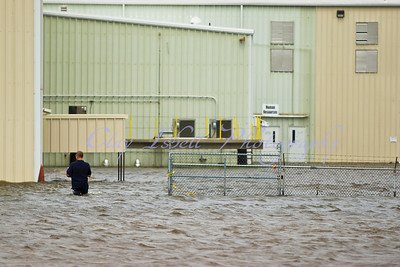 A man walks into a flooded business in eastern New Orleans.