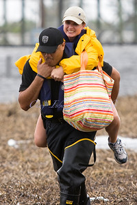 An NOPD officer carries a woman to higher ground along flooded Hwy 90 in eastern New Orleans.