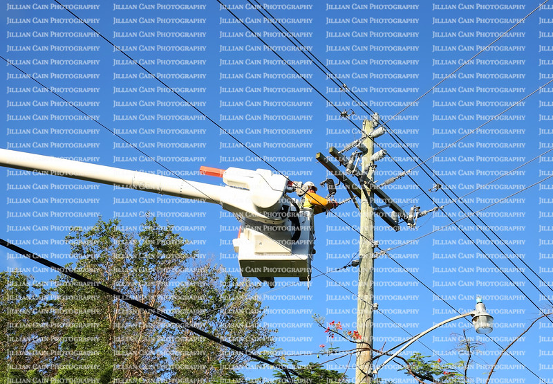 Power worker connects the main line in a residential neighborhood that was left in the dark for 6 days after Hurricane Irma hit.