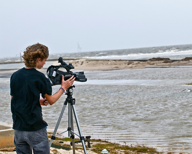 Young man is making a video remembrance of the Gulf over Hwy 90.