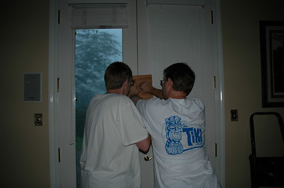 7.  This was the scariest part of the storm just before the eye.  We had gone into the library in case the windows on the south side of the house blew.  I noticed the french doors in the great room and master bedroom bowed in and fixin to blow.  Water was spewing in around them.  I tried to yell for them to come and only a hoarse sound came out.  David and David are shown here boarding them up.  Yea, even though I was petrified for my home, I was still able to grab my trusty Nikon!