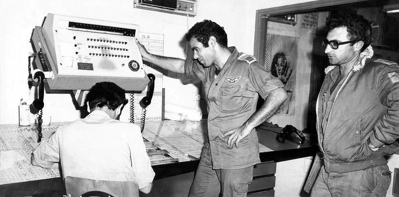 ה-7 באוקטובר, היום השני למלחמה - אחרי שהטייסת מקבלת את המשימה, גף הטיסה מעביר לגף הטכני הנחיות חימוש וזמנים. בתמונה הבאה: קציני הגף הטכני, לוט ו ג'ימי, בהנחיות אחרונות להתאמת הנדרש למצאי המטוסים. (מתוך האוסף של יוסי יערי) .