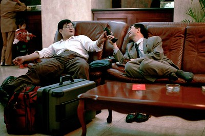 China.  Urumqi.  Chinese business men in lobby of City Hotel use portable phone. Suitcases.  Luggage.