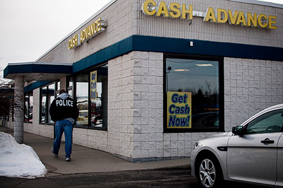 Charlotte Bodak/Staff Photographer   Mount Pleasant Police Officer walks alongside the Cash Advance where an armed robbery took place shortly after 2:00 p.m. Monday afternoon, 100 South Mission.
