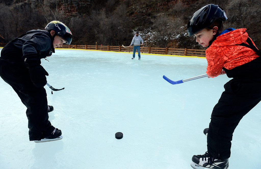 . LYONS , CO JANUARY 6, 2019 Twin brother, Dalton and Colby Andrews, 7, at right, face off on the ice rink at LaVern M. Johnson Park in Lyons on January 6, 2019. Their dad Brian Andrews can be seen in the background.  For more photos go to dailycamera.com  (Photo by Paul Aiken/Staff Photographer)